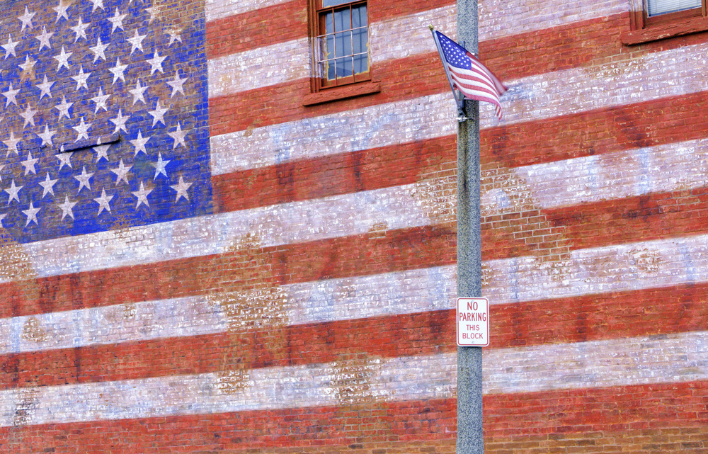 Small-town street scene in Illinois American flag flapping in breeze by huge painted American flag fading from brick wall